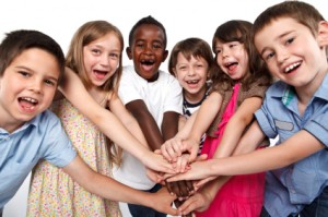 Multiracial children putting their hands together